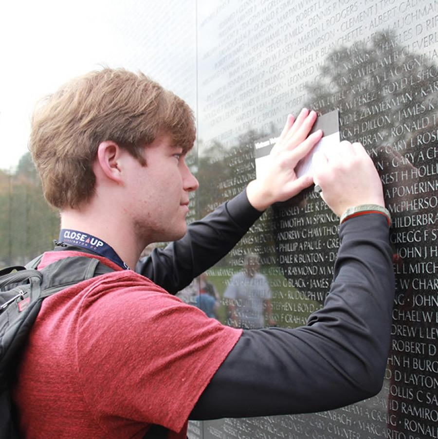 High school male student learning at Vietnam Memorial in Washington, DC