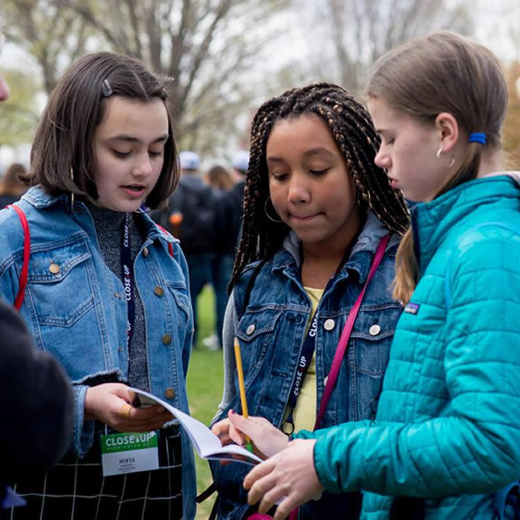 Middle school girls reading notebook on National Mall
