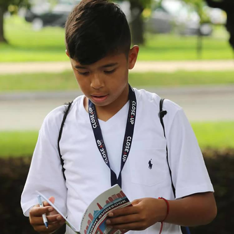 Middle school male reading Close Up guidebook while on program in Williamsburg, VA