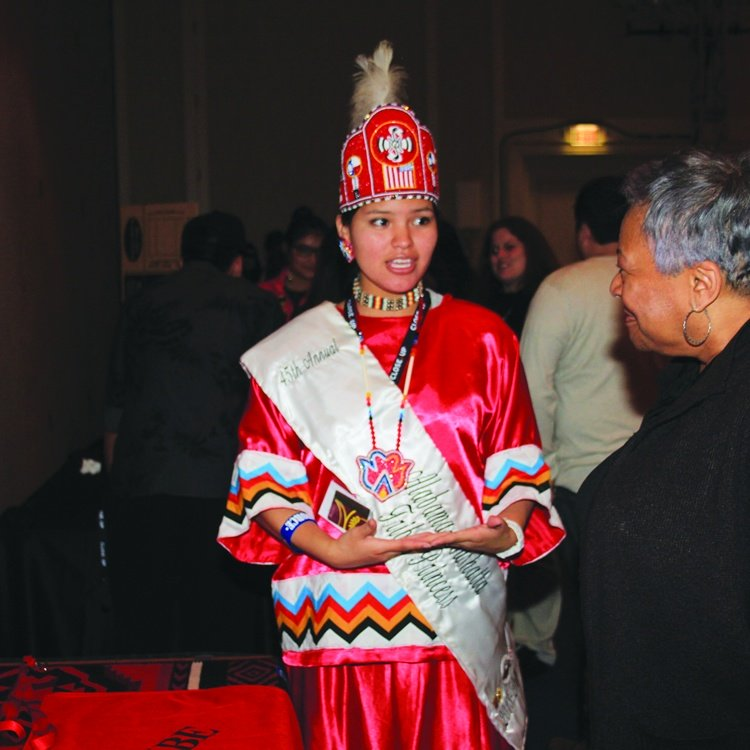 American Indian female student presenting in red tribal clothing on American Indian program