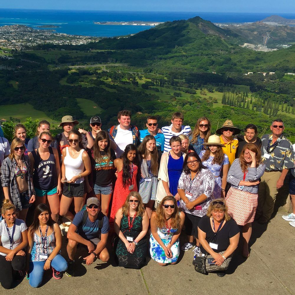 Group of high school students posing on a mountain top with beautiful views in Hawaii