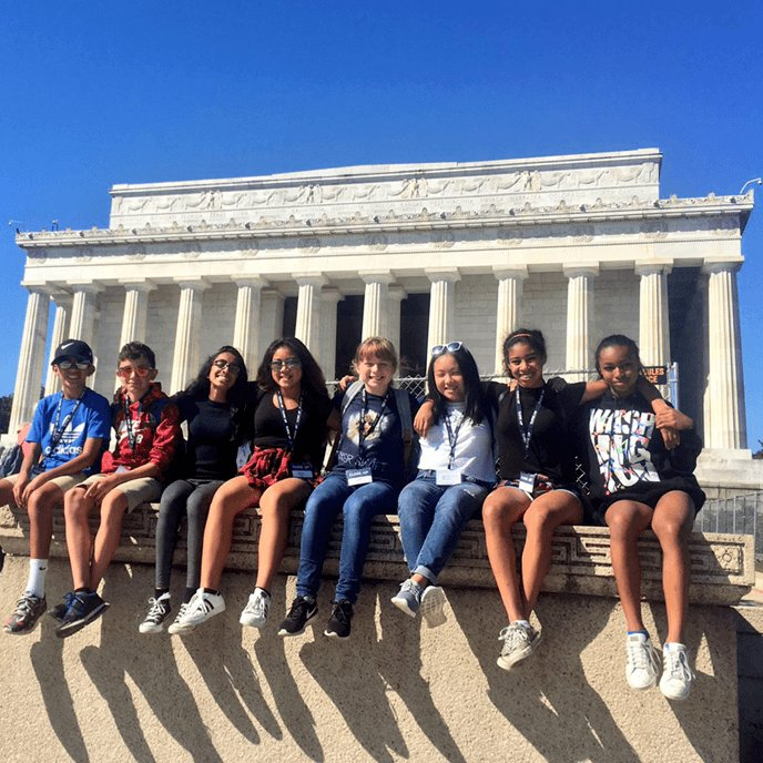 Middle school students posing on sunny day in front of Lincoln Memorial